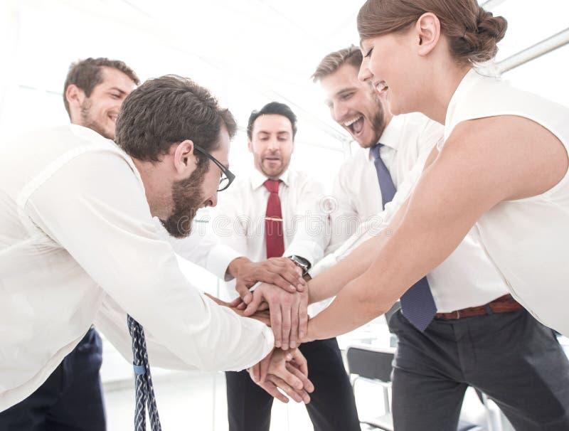 I colleghi felici collega insieme le loro mani fotografia stock