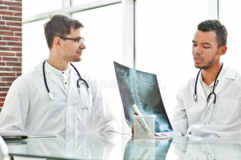 I colleghi medici discutono i raggi x, sedentesi alla tavola dell'ufficio fotografia stock libera da diritti