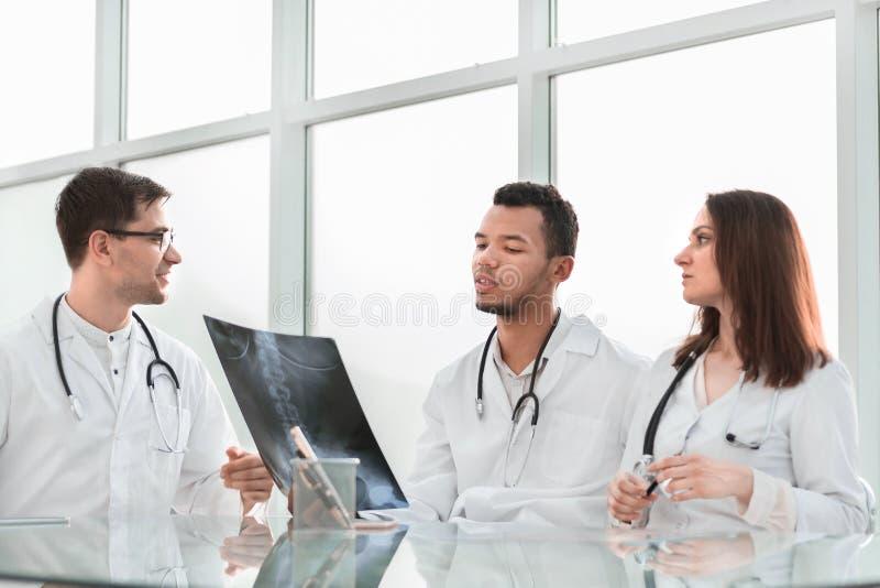 I colleghi medici discutono i raggi x, sedentesi alla tavola dell'ufficio immagine stock