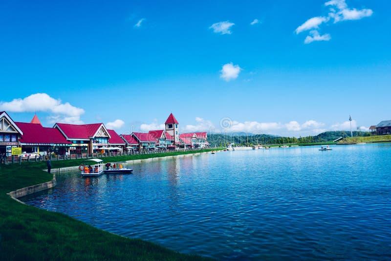 I colori dell'acqua e del cielo si complementano e una fila delle ville è punteggiata fra loro fotografie stock