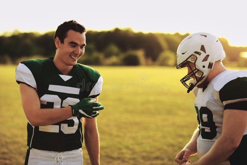 I compagni di calcio sorridenti parlano dopo un allenamento di tardo pomeriggio fotografia stock