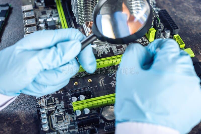 I computer del tecnico dell'ingegnere in guanti sulle mani sta esaminando il guasto Concetto del microchip di riparazione immagini stock
