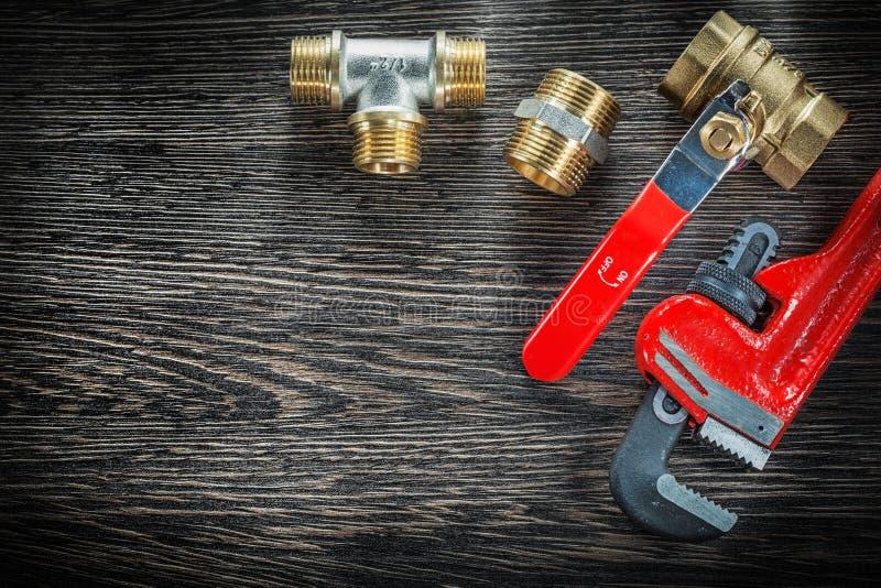 I connettori della chiave inglese dell'impianto idraulico innaffiano la valvola su di legno d'annata fotografia stock