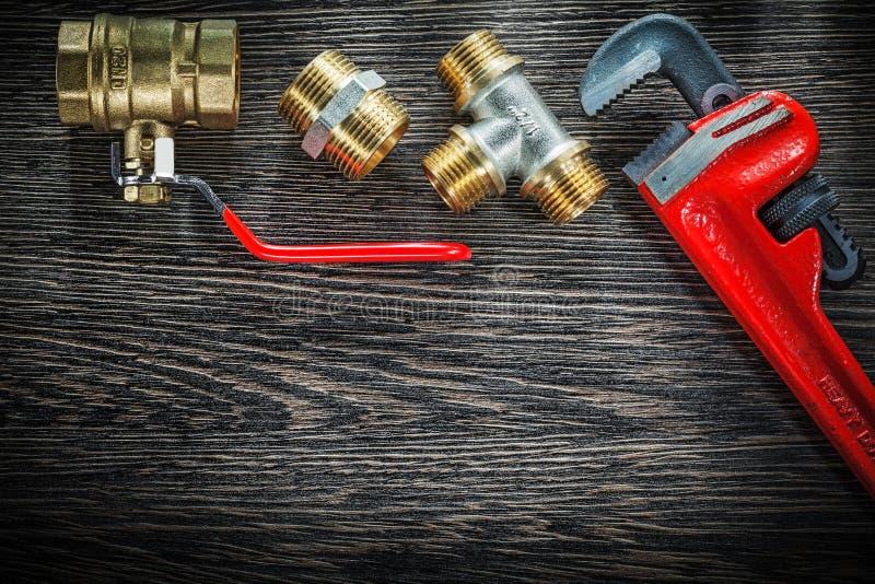 I connettori della chiave stringitubo dell'impianto idraulico innaffiano la valvola sulla BO di legno d'annata immagini stock