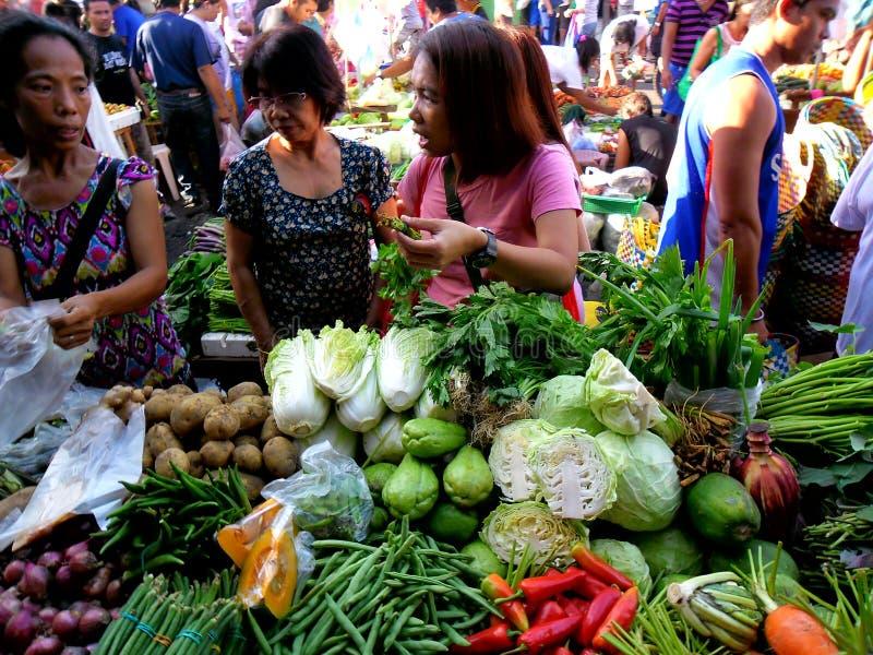 I consumatori comprano da un venditore di verdure in un mercato in Cainta, Rizal, le Filippine, Asia fotografie stock