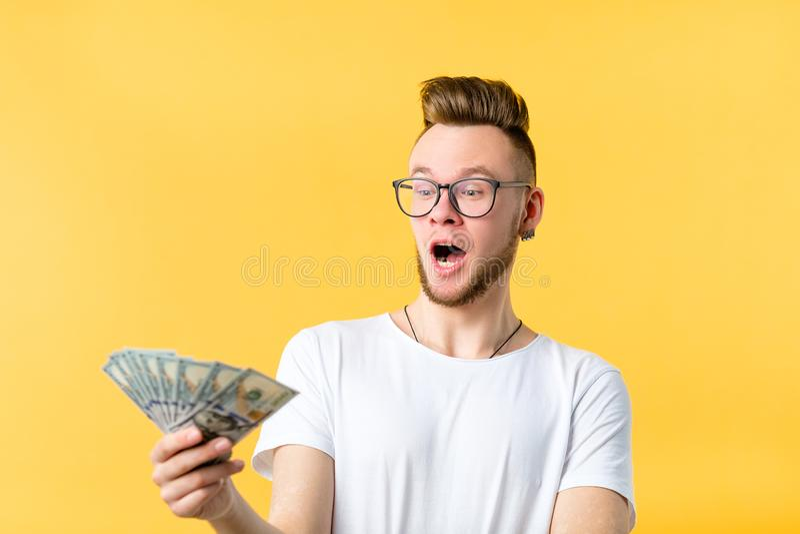 I contanti del dollaro del giovane hanno sorpreso la ricompensa di pagamento fotografie stock