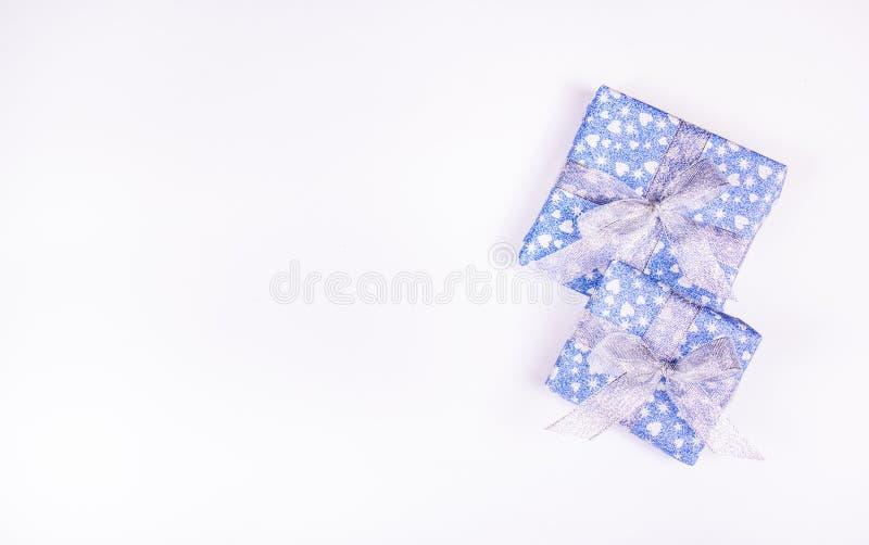 I contenitori di regalo blu con argento si piega su un fondo bianco Concetto celebratorio Scatole brillanti fotografia stock libera da diritti