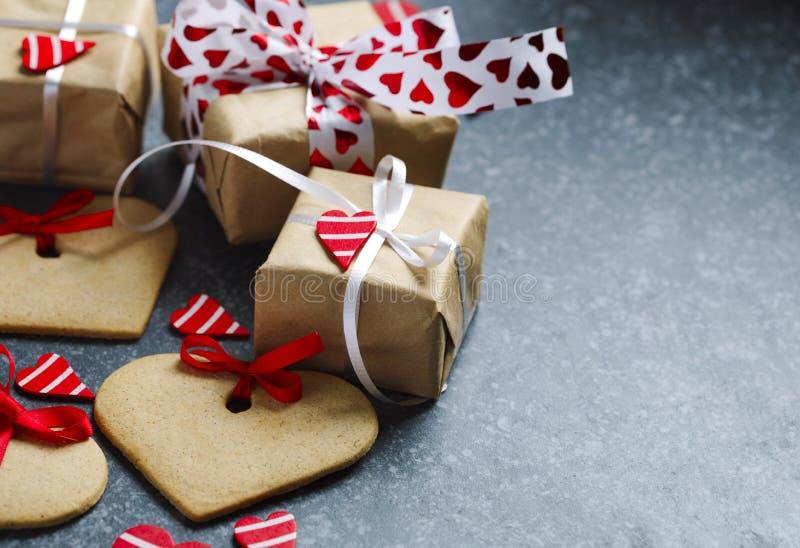 I contenitori di regalo con i cuori ed il cuore rossi decorativi hanno modellato i biscotti fotografia stock libera da diritti