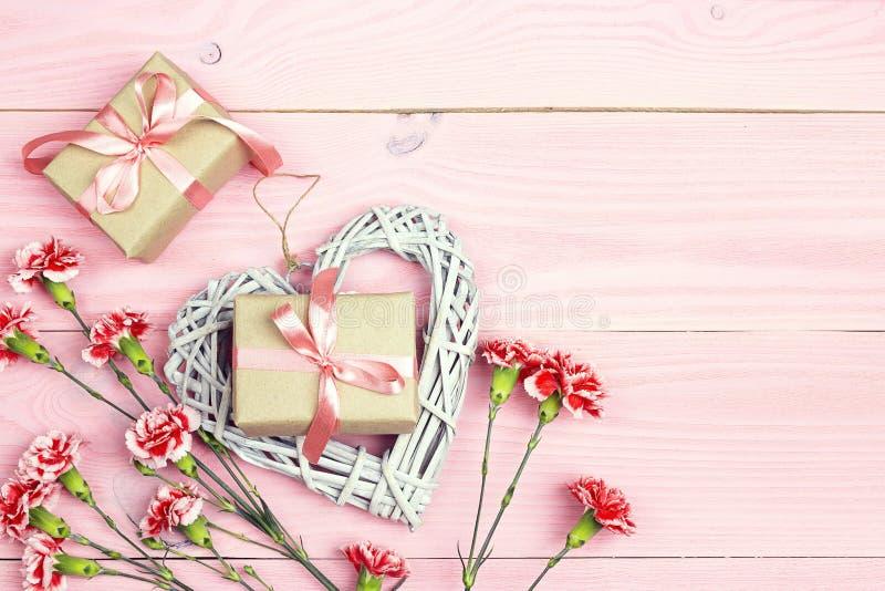 I contenitori di regalo con i garofani fiorisce su fondo di legno rosa Copi lo spazio fotografie stock libere da diritti