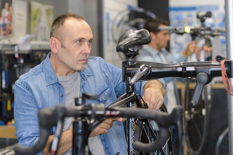 I controlli dell'uomo bike prima dell'acquisto nel negozio di sport fotografie stock libere da diritti