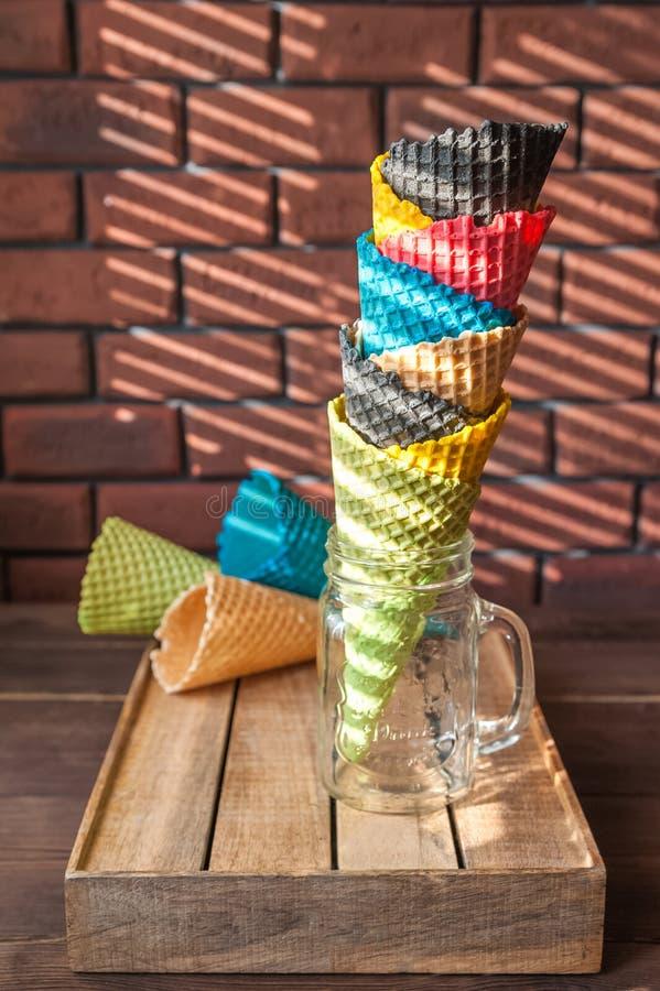 I corni multicolori per il gelato in un barattolo stanno su una scatola di legno in un modello di contrapposizione dell'ombra dai fotografia stock