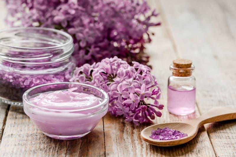 I cosmetici lilla con i fiori e la stazione termale hanno messo sul fondo di legno della tavola fotografia stock libera da diritti