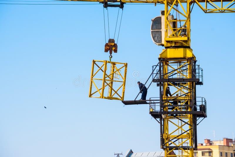 I costruttori lavorano alla gru gialla al cantiere fotografie stock
