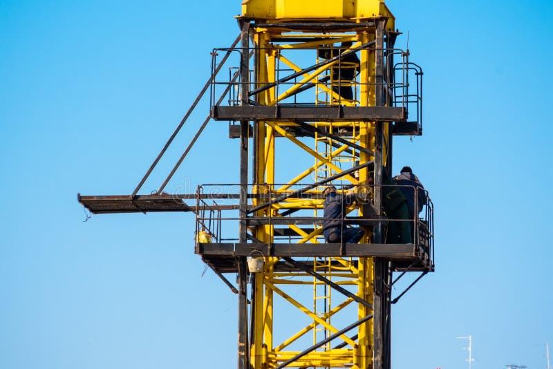 I costruttori lavorano alla gru gialla al cantiere immagini stock