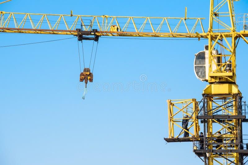 I costruttori lavorano alla gru gialla al cantiere fotografia stock