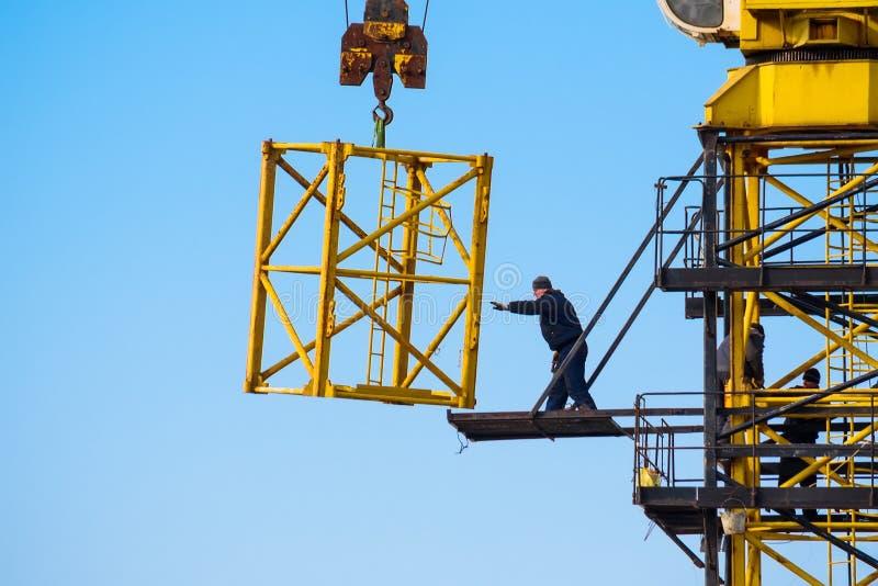 I costruttori lavorano alla gru gialla al cantiere immagine stock libera da diritti
