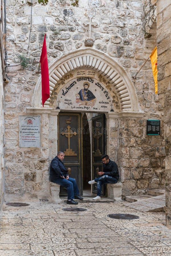 I credenti si siedono vicino all'entrata alla chiesa di St Mark - la chiesa ortodossa siriana in vecchia città di Gerusalemme, Is fotografia stock