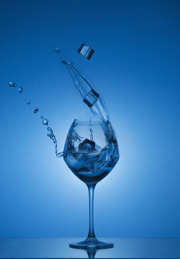 I cubetti di ghiaccio cadono in un vetro e l'acqua è versata fuori Acqua che spruzza da un vetro di vino alto fotografia stock