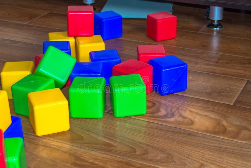 I cubi di plastica variopinti per i giochi dei bambini sono sparsi sul pavimento di legno immagini stock libere da diritti