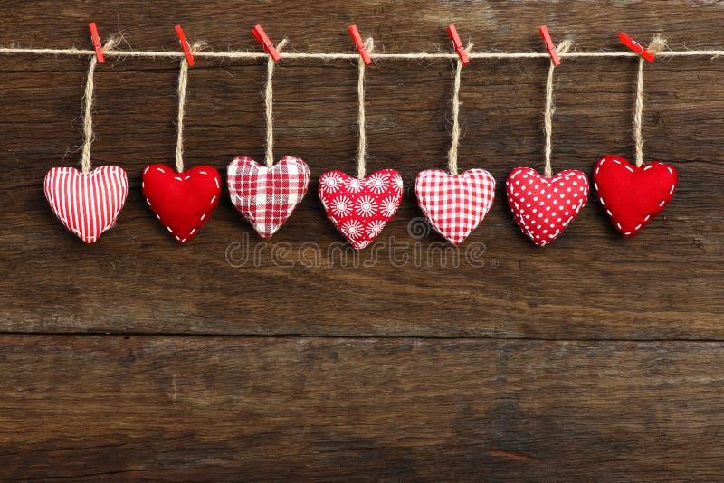 I cuori del biglietto di S. Valentino di amore del percalle che appendono sul backgr di legno di struttura immagine stock