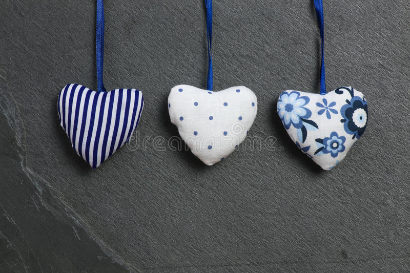 I cuori del modello del biglietto di S. Valentino blu bianco di amore che appendono sull'ardesia grigia fotografie stock