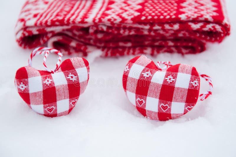 I cuori della decorazione dell'albero si avvicinano alla sciarpa rossa fotografia stock