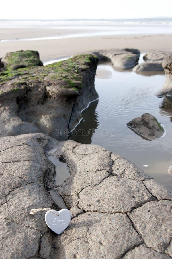 I cuori di legno singoli di amore sulla sabbia contano fotografia stock libera da diritti