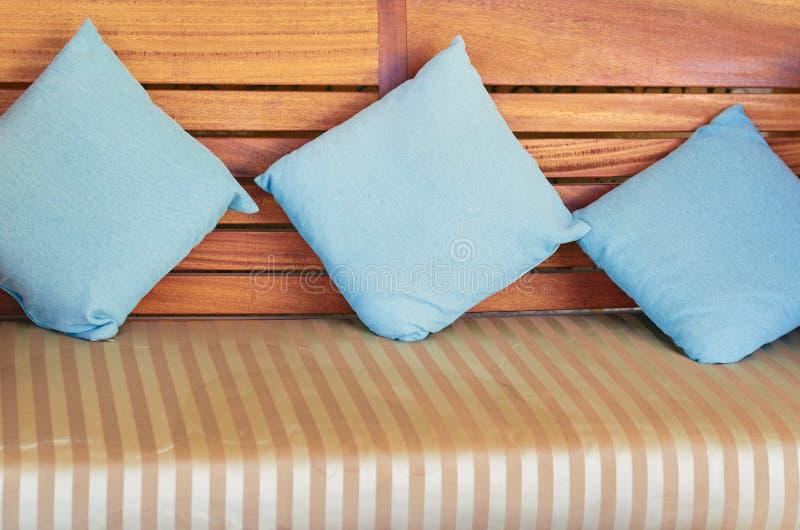 I cuscini blu del cotone si trovano su uno strato di legno immagine stock