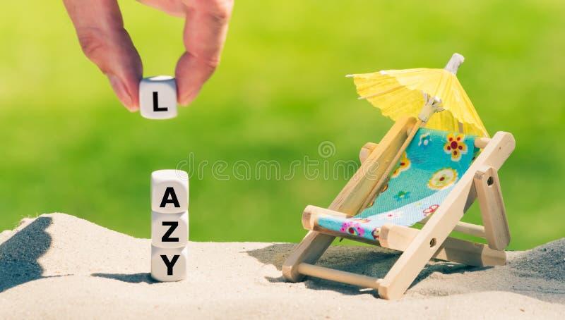 """I dadi hanno disposto accanto ad una forma della sedia di spiaggia la parola """"pigra """" fotografie stock"""