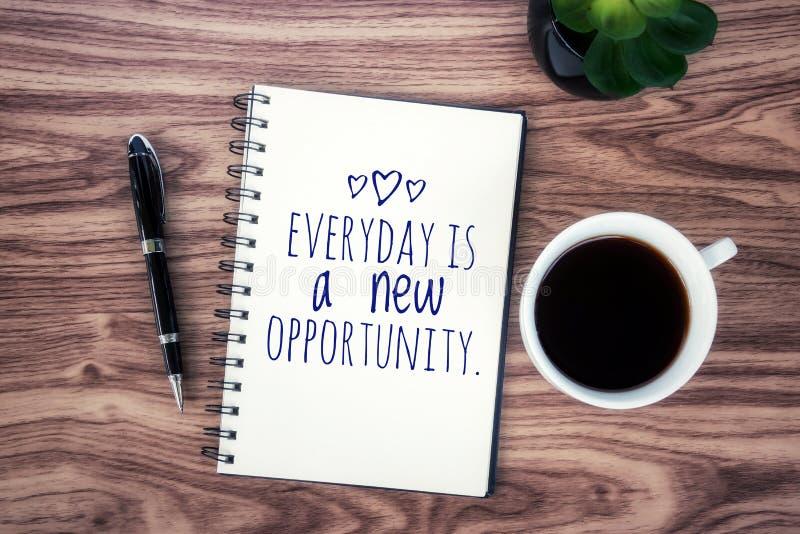 I dag är det dagliga inspirerande citationstecknet ett nytt tillfälle Med positiv motivational text på en anteckningsbok en kopp  royaltyfri fotografi