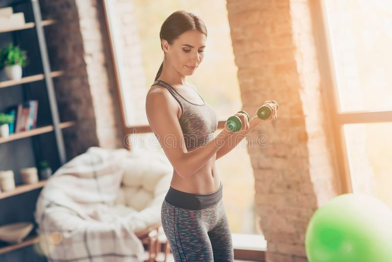 I dedicate my freetime to my health! Side profile view photo of. Attractive powerful muscular woman holding green dumbbells in hands trying to built muscle mass royalty free stock photography