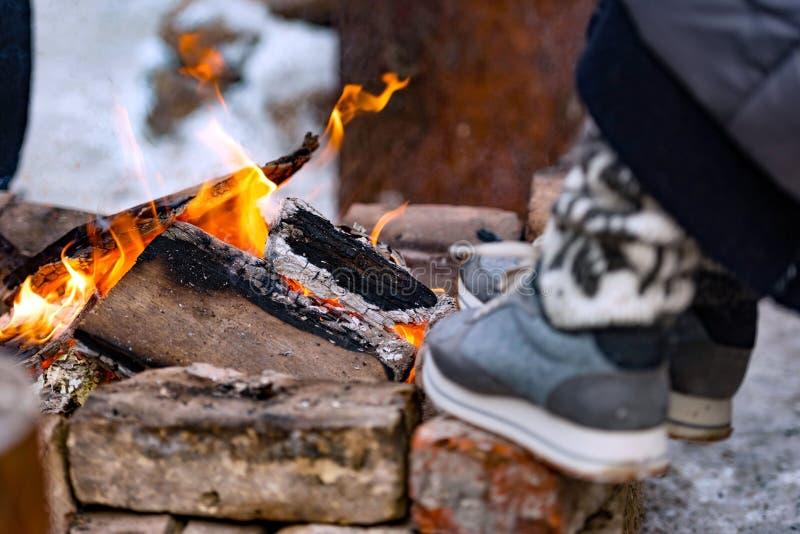 I den kalla vinterdagen värmer en person fot till branden arkivbilder