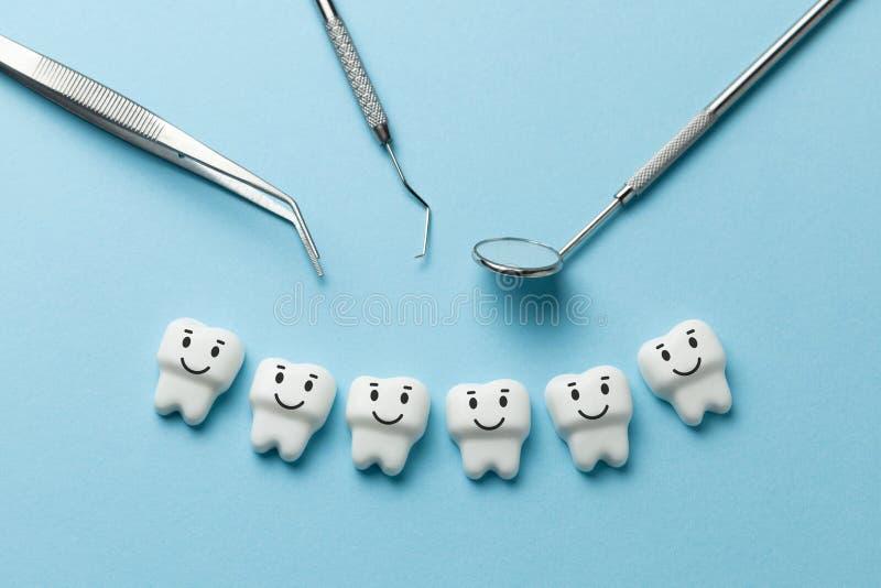 I denti bianchi sani stanno sorridendo sugli strumenti blu lo specchio, gancio del dentista e del fondo fotografia stock