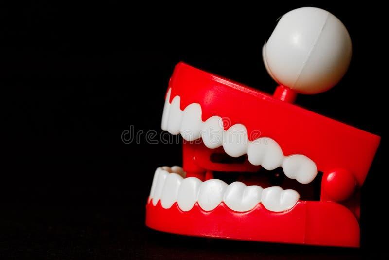I denti di schiamazzo giocano dal lato con la bocca aperta immagine stock