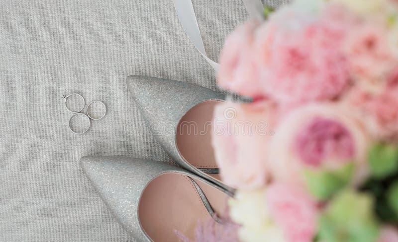 I dettagli di lusso di nozze sono scarpe della sposa e delle fedi nuziali da platino fotografie stock libere da diritti