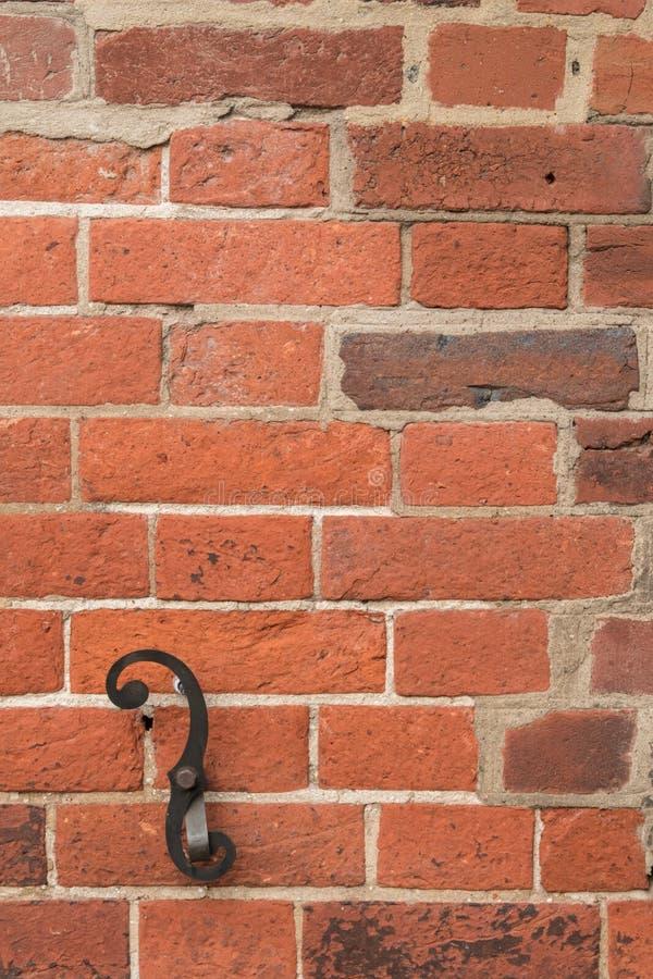 I dettagli rivestono di ferro l'ornamento del rotolo allegato al muro di mattoni stagionato - struttura, fondo, orientamento vert fotografia stock