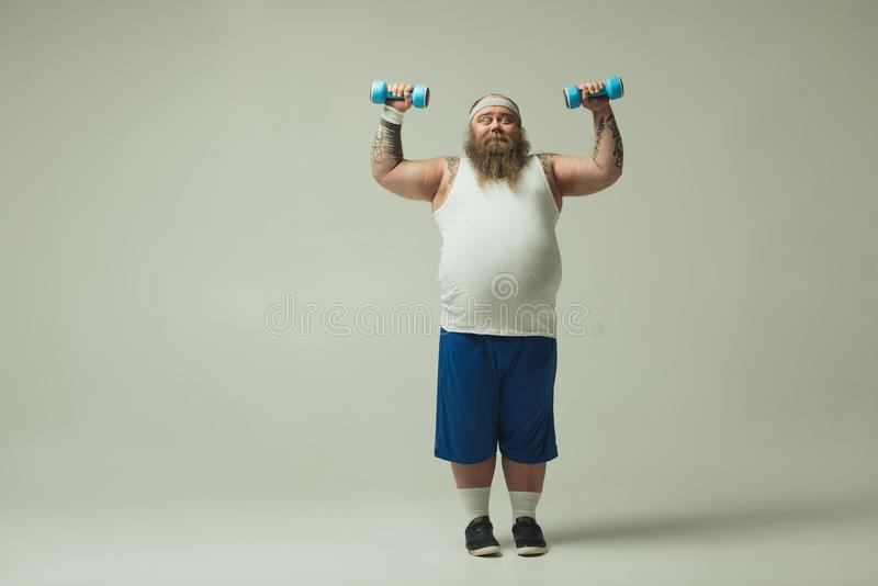 Strained male raising dumbbells up with effort stock image