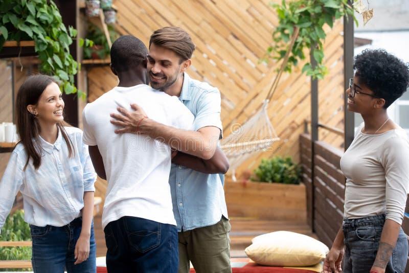 I diversi amici maschii felici abbracciano la riunione alla riunione amichevole fotografie stock libere da diritti