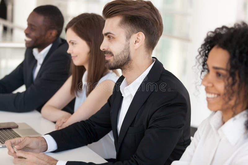 I diversi reclutatori millenari si siedono alla tavola che gradiscono il cand di intervista immagine stock libera da diritti