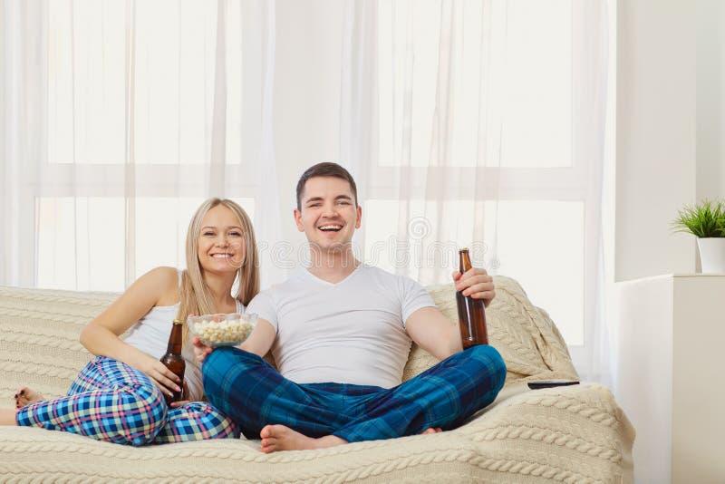 I divertimenti delle coppie con la bottiglia guardano la TV sedersi sul sofà nella sala fotografia stock