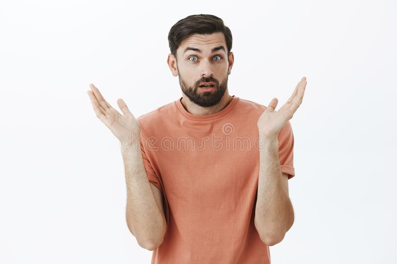 I do not know how it happened. Portrait of confused and questioned surprised attractive unaware guy with beard opening. Mouth and raising eyebrows from royalty free stock images