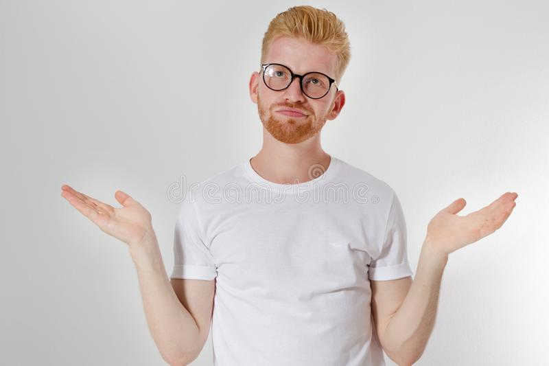 I do not know what to choose concept, European- looking red hair man of 30 years with glasses and white t-shirt, does not know stock images