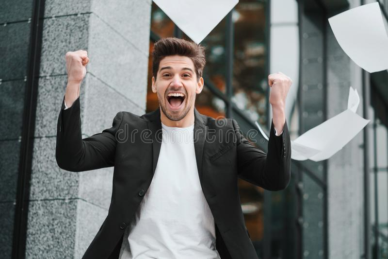 I documenti di carte di lancio dell'uomo d'affari in aria e celebra il successo sul fondo dell'edificio per uffici Libertà, riusc immagini stock
