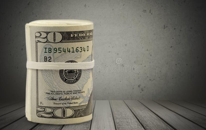 I dollari rotolano stretto con la banda sulla tavola di legno fotografia stock libera da diritti