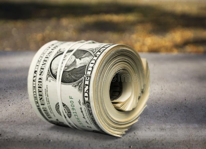 I dollari rotolano stretto con la banda sulla tavola di legno immagini stock