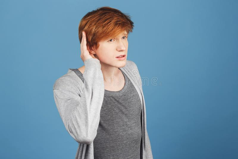 I don`t hear you. Copy space. Close up of serious good-looking guy with red hair in casual clothes holding hand near ear stock image