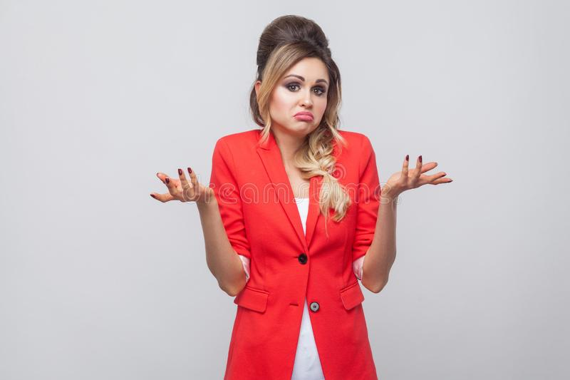 I don`t know. Doubtful beautiful business lady with hairstyle and makeup in red fancy blazer, standing with raised arms and. Looking at camera with confused royalty free stock photography