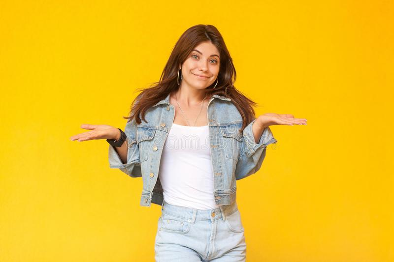I don`t know. Portrait of confused beautiful brunette young woman with makeup in denim casual style standing with raised arms and. Looking at camera. indoor stock images