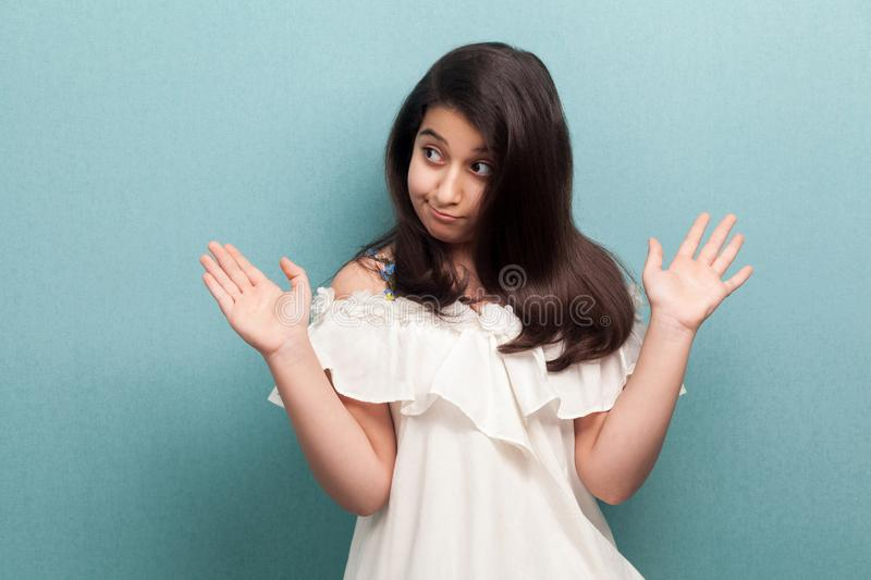 I don`t know. Portrait of confused beautiful young girl with black long straight hair in white dress standing with raised arms royalty free stock photo