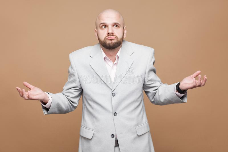 I don`t know! Portrait of confused crossed hands handsome middle. Aged bald bearded businessman in classic light gray suit standing and thinking. indoor studio stock photos